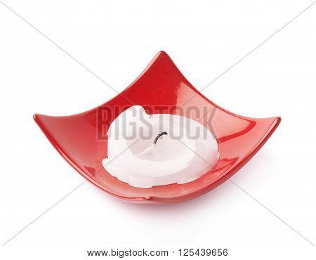 Burned melt down white parafine candle in a red square plate isolated over the white background