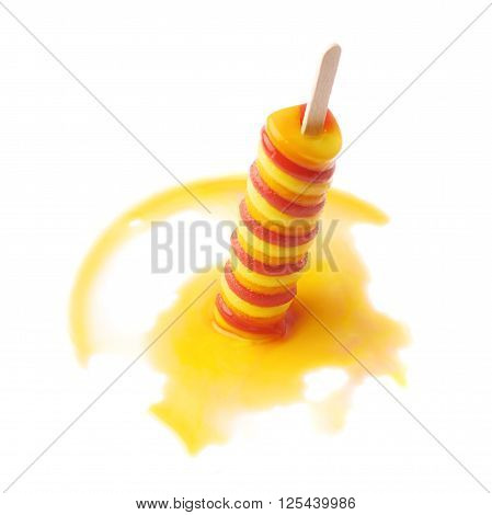 Colorful, twisted frozen fruit juice ice pop popsicle snack on a wooden stick shot in a process of melting down, composition isolated over the white background