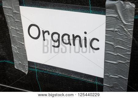 Laminated Organic Sign In Comic Sans Taped To Dark Background