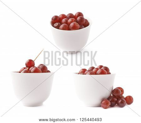 White ceramic cup filled with the dark red grapes isolated over the white background, set of three different foreshortenings