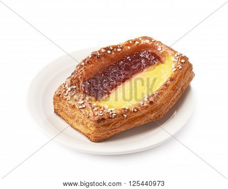 Sweet bread bun pastry filled and covered with the red and yellow cream filling in a white ceramic plate, isolated over the white background