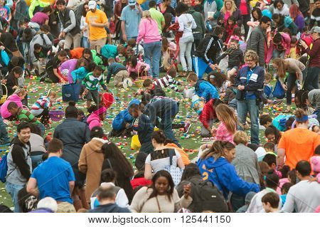 MARIETTA, GA - MARCH 2016: Kids and parents eagerly grab plastic eggs and candy at the start of a massive community Easter egg hunt at a local high school in Marietta GA on March 26 2016.