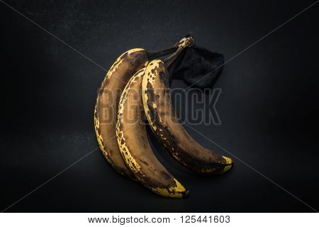 Great amazing detailed closeup view of old stained expired banana fruits isolated on dark grey background