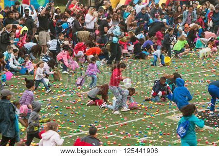 MARIETTA, GA - MARCH 2016:  Kids and parents eagerly dash out onto the football field at the start of a massive community Easter egg hunt at a local high school in Marietta GA, on March 26 2016.