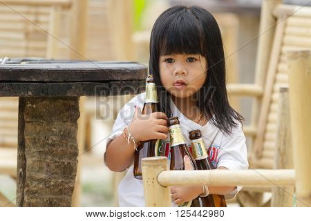 KO PHANGAN, THAILAND, FEBRUARY 21, 2011 : A little girl is holding three beers bottles for clearing the table of her parent's restaurant in the Ko Phangan island, Thailand.