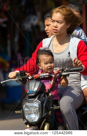 THONG PHA PHUM, THAILAND, JANUARY 23, 2016 : Three adults and a child are riding a scooter without helmet protection in the street of Thong Pha Phum, Thailand.