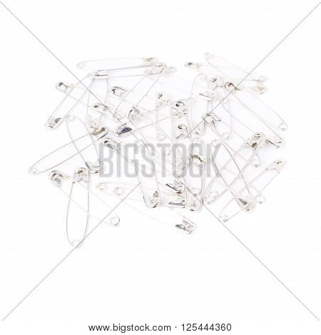 Surface covered with multiple metal safety pins isolated on white background