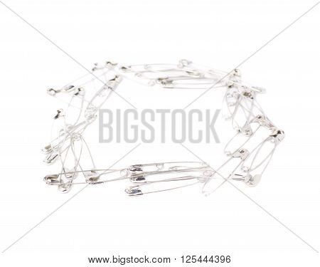 Square frame made of metal safety pins isolated on white background