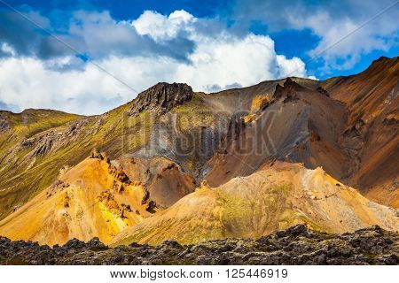 Multicolored rhyolite mountains highlights the July sun. Travel to Iceland in the summer. National Park Landmannalaugar
