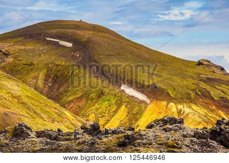 Incredible shades of rhyolitic mountains - yellow, orange, green and blue. Summer volcanic tundra.  Travel to Iceland in July