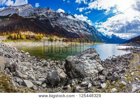Stony shore shoaled Medicine Lake. Autumn in Jasper National Park, Canada