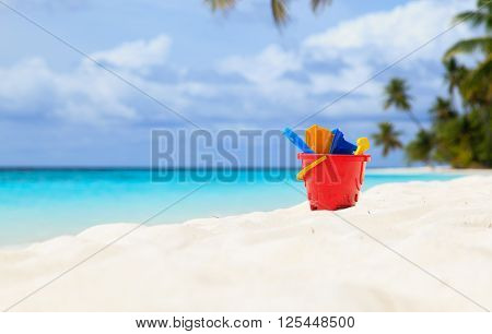 kids toys on white sand beach, family vacation