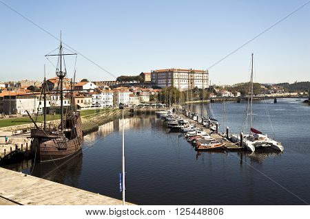 VILA DO CONDE, PORTUGAL - September 20, 2015: View of the river mouth marina with the replica of a sixteenth century caravel on the left on September 20, 2015 in Vila do Conde, Portugal