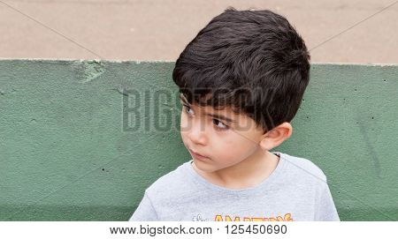 Boy looking sideways with green wall behind