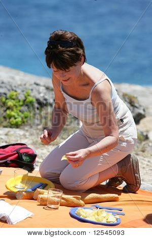 Portrait of a senior woman picnicking on the seafront