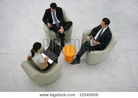 Portrait of business people sitting on armchairs with laptop computers and a phone