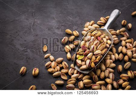 Pistachios in a scoop on a dark background. Food background Top view