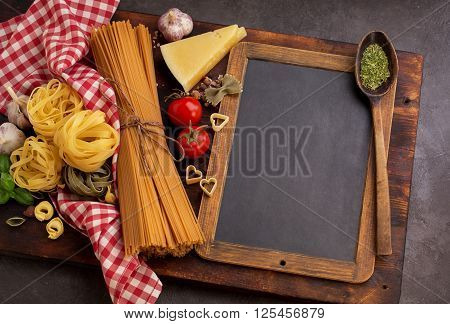 Different pasta and blackboard for recipes or food menu