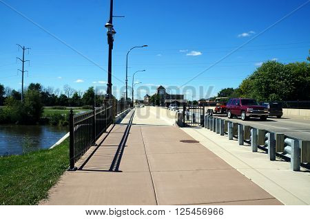 PLAINFIELD, ILLINOIS / UNITED STATES - SEPTEMBER 20, 2015: Pedestrians and vehicles may cross a bridge over the DuPage River in downtown Plainfield, Illinois.