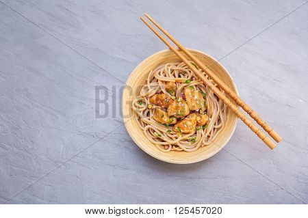 Noodles with chicken and sesame seeds. Asian Cuisine background with copyspace