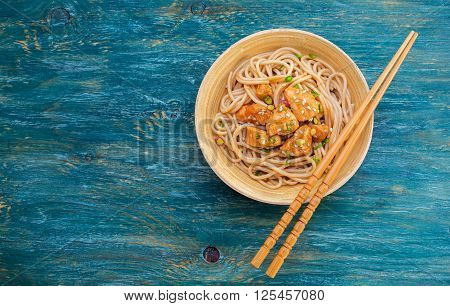 Noodles with chicken and sesame seeds. Food background with copyspace
