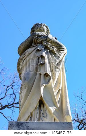 Haunting Statue of a lady or angel in a white robe standing as if guarding over and watching.