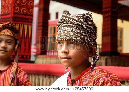 Young Boy In Traditional Clothes At Funeral Ceremony. Tana Toraja
