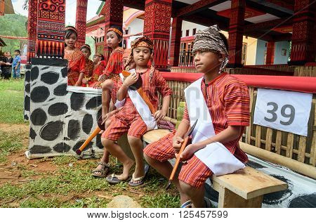 Group Of Young Girls Boys In Traditional Clothes At Funeral Ceremony. Tana Toraja