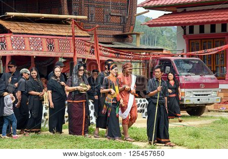 Group Of People In Black At Funeral Ceremony. Tana Toraja