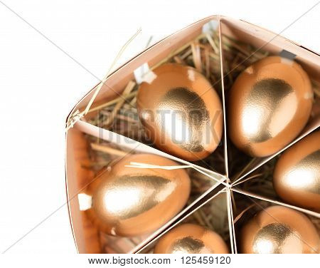 golden eggs in a basket on white background