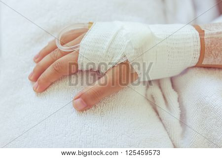 Saline Intravenous (iv) Drip In A Child's Patient Hand.