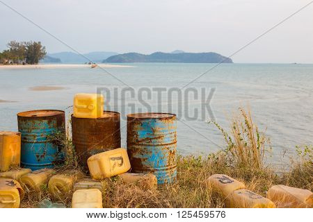 Three rusty barrels and plastic canisters next to a a tropical beach in Malaysia