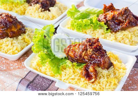 Fried satay chicken with rice and salad on a food market in Malaysia