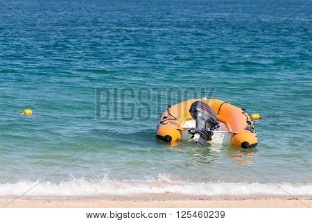 Inflated plastic speed boat floating on the shallow beach