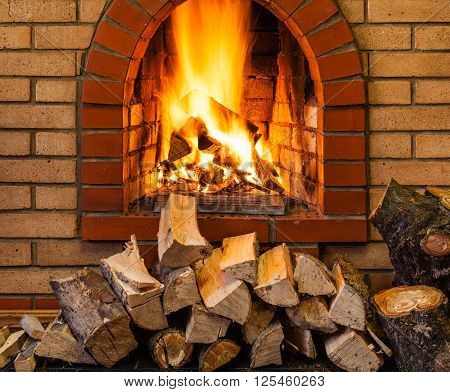 Stack Of Firewood And Fire In Brick Fireplace