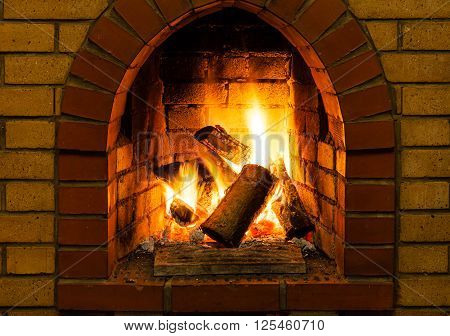 Burning Wooden Logs In Brick Fireplace