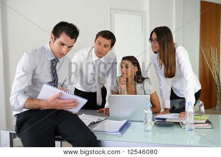 Portrait of young business people with a laptop computer and documents