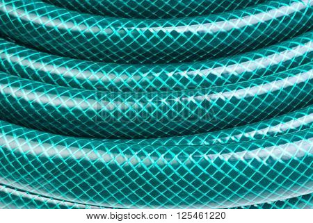 green hose close-up for watering as background