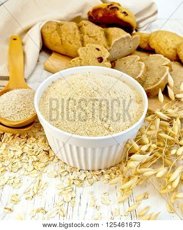 Flour Oat In White Bowl With Bran In Spoon On Board