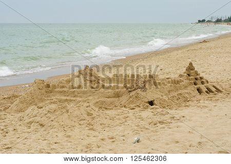 Grand sand castle on an empty beach.