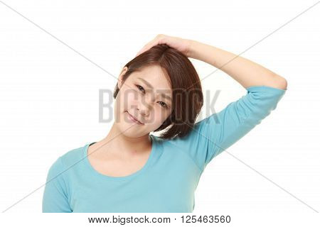 studio shot of young woman doing self neck stretch