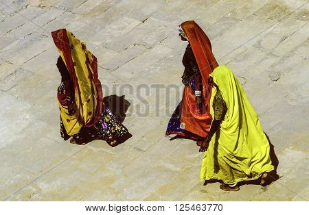 Women In Traditional Clothes Walk Barefoot In The Temple Area In Jaisalmer