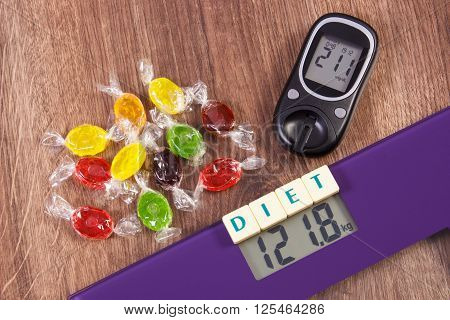 Electronic bathroom scale and glucose meter with high result of measurement weight and sugar level and heap of colorful candies diabetes slimming and reduction eating sweets