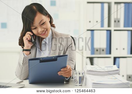 Smiling Vietnamese businesswoman talking on the phone when looking at document