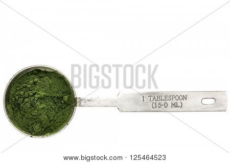Nutrient-rich organic spirulina  powder - isolated measuring metal tablespoon, top view