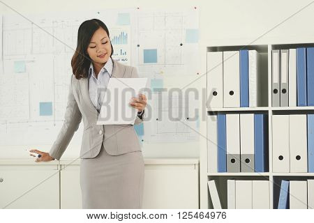 Female real estate broker reading contract in office