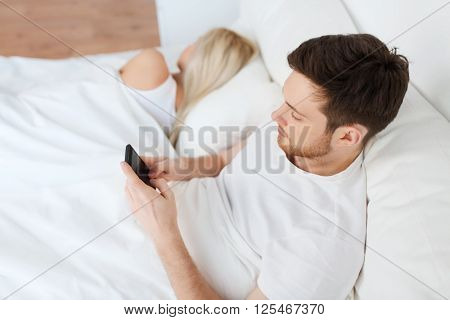 people, technology, internet and communication concept - man with smartphone texting message while woman is sleeping in bed