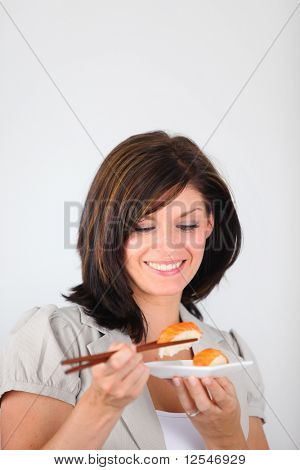 Portrait of a young woman eating sushi with chopsticks on white background