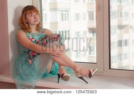 girl in a bright dress on a window sill