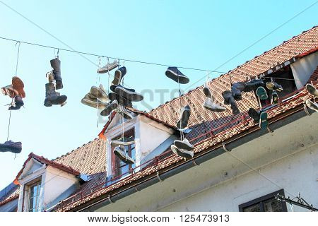Shoes hanging by shoelaces on a wire above